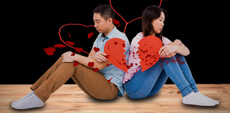 lose up: Sad couple holding broken heart pieces against red hearts floating Stock Photo