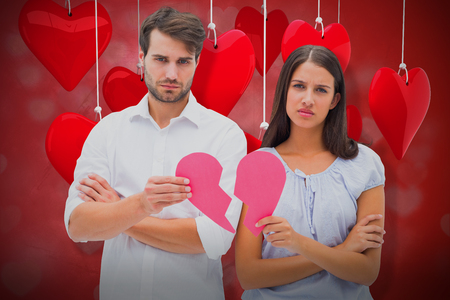 Upset couple holding two halves of broken heart against valentines heart design 3d Stock Photo