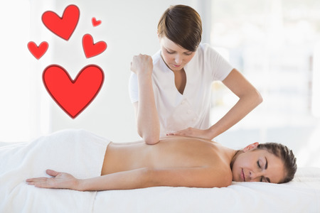 masseuse giving massage to relaxed woman