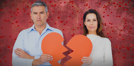 Portrait of couple holding broken heart shape paper against red paint splashed surface