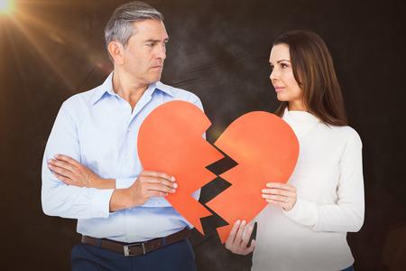 strife: Couple holding broken heart shape paper against grey