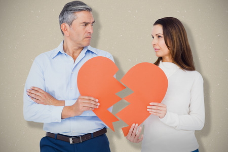 Couple holding broken heart shape paper against grey