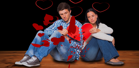strife: Young couple sitting on floor with broken heart against red hearts floating Stock Photo