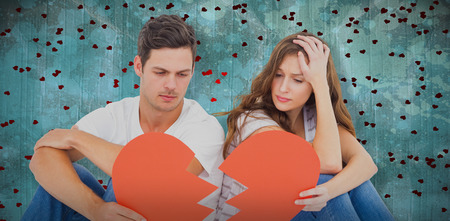 Young couple sitting on floor with broken heart shape paper against blue paint splashed surface