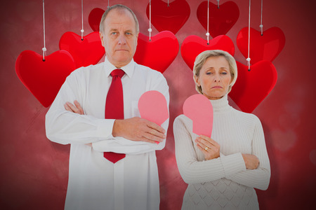 Older couple standing holding broken pink heart against valentines heart design 3d
