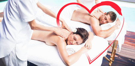 young couple receiving back massage from masseur Stock Photo