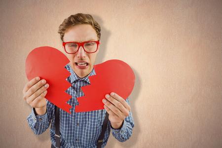 geeky: Geeky hipster holding a broken heart  against a beige wall