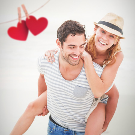 Hearts hanging on a line against man giving piggy back to woman at beach Stock Photo