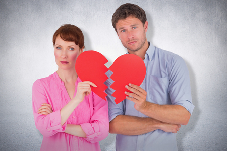 Couple holding a broken heart against white wall Stock Photo