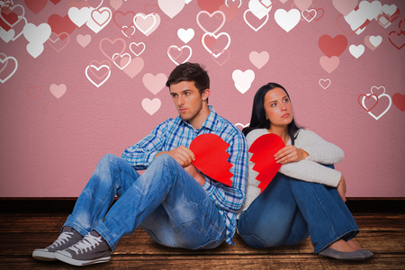 Young couple sitting on floor with broken heart against gray concrete wall