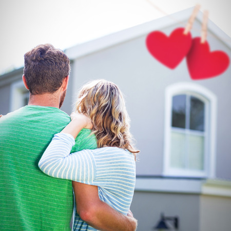 Hearts hanging on a line against couple standing against house