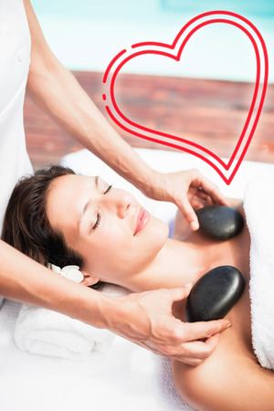 woman receiving hot stone massage from masseur Stock Photo