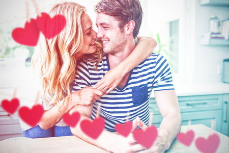 Hearts hanging on a line against couple embracing in kitchen Stock Photo