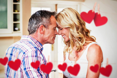 Hearts hanging on a line against couple touching foreheads at home Stock Photo
