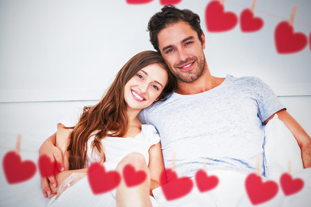 Hearts hanging on a line against portrait of happy couple leaning on bed Stock Photo