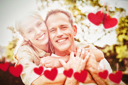 Hearts hanging on a line against couple with arms around Stock Photo