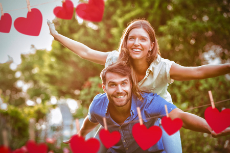 Hearts hanging on a line against smiling young couple having fun