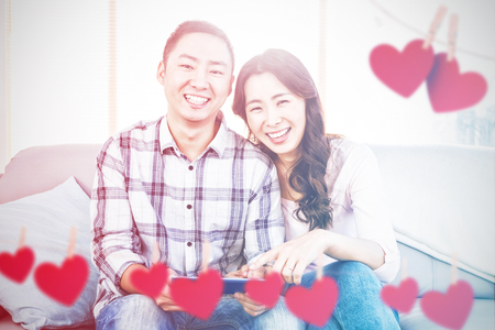 Hearts hanging on a line against young happy couple holding digital tablet