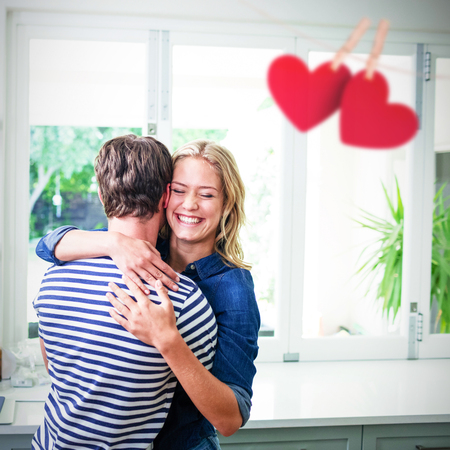 Hearts hanging on a line against couple hugging in kitchen Stock Photo