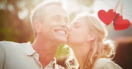 Hearts hanging on line against wife kissing husband on cheek