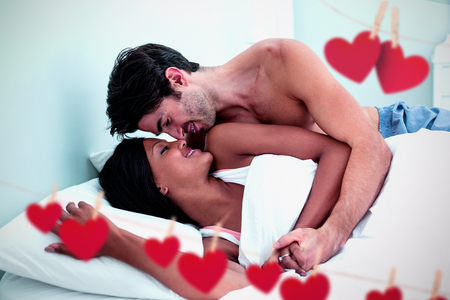Hearts hanging on a line against young couple embracing while lying on bed Stock Photo