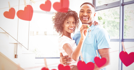 Hearts hanging on a line against portrait of happy couple embracing in their new home Stock Photo
