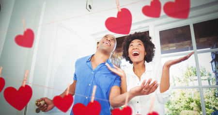 Hearts hanging on a line against happy couple entering home