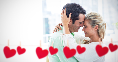 Hearts hanging on a line against romantic couple embracing at home