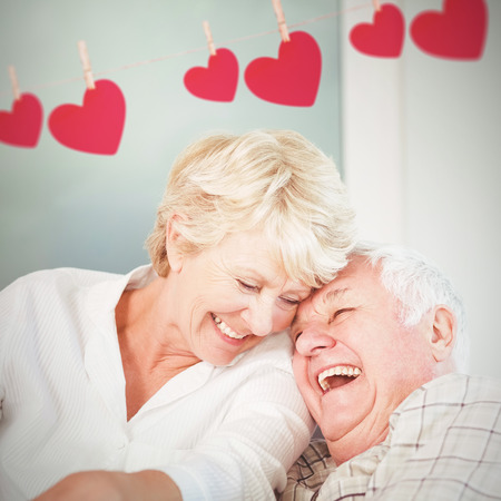 70s: Hearts hanging on a line against cheerful senior couple laughing