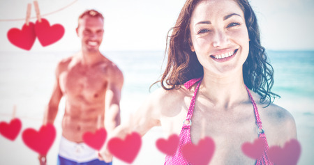 Hearts hanging on a line against happy young couple holding hand on beach Stock Photo