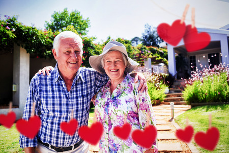 Hearts hanging on a line against portrait of happy senior couple in garden