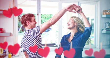 Hearts hanging on a line against cute couple dancing