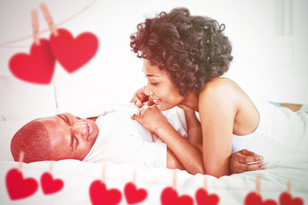Hearts hanging on a line against happy couple lying on bed