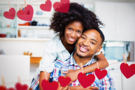 Hearts hanging on a line against portrait of young couple embracing in kitchen Stock Photo