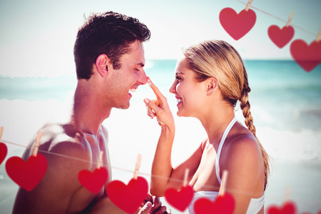 Hearts hanging on a line against couple having fun on beach