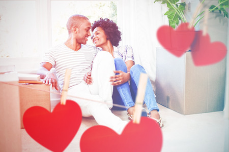 Hearts hanging on a line against happy couple sitting on floor