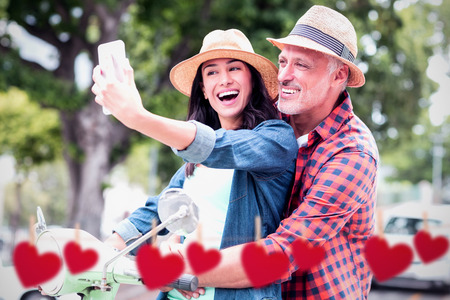 Hearts hanging on a line against happy couple taking selfie on moped