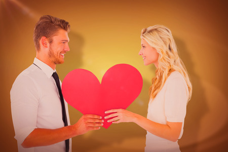 Attractive young couple holding red heart against yellow vignette