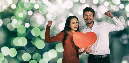 Cheerful couple holding paper heart against glowing background