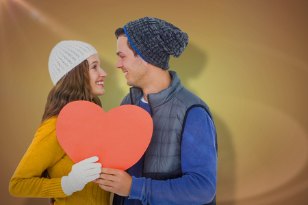 Happy couple holding paper heart against yellow vignette