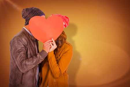 Happy young couple holding heart shape paper against yellow vignette