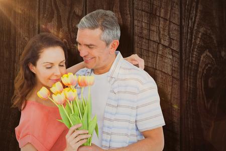 mujer con rosas: sonriente pareja con el ramo de flores contra la madera Foto de archivo