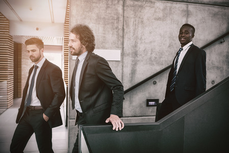 down the stairs: Group of businessmen climbing down stairs in office