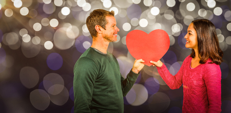 Smiling couple holding red heart shape  against glowing background Stock Photo