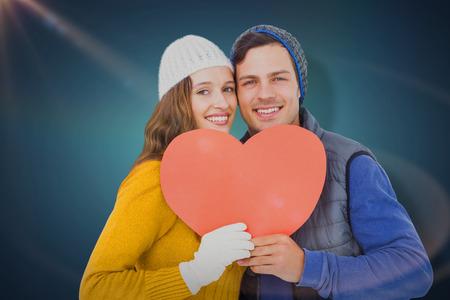Portarit of happy couple holding paper heart against blue vignette background