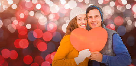 Portarit of happy couple holding paper heart against glowing background