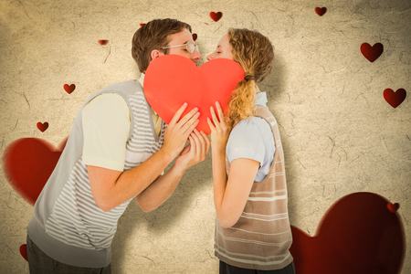 together with long tie: Geeky hipster couple kissing behind heart card against love heart pattern
