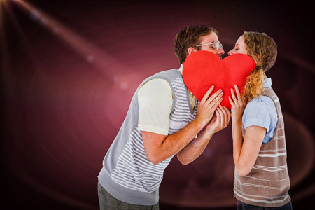 together with long tie: Geeky hipster couple kissing behind heart card against red vignette