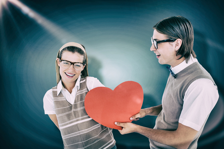 geeky: Geeky hipster offering red heart to his girlfriend  against blue vignette background Stock Photo