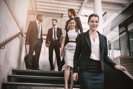 down the stairs: Empresaria confidente con los colegas que suben por las escaleras en la oficina